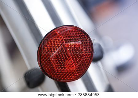 Close-up Of A Red Backlight And Red Safety Reflector Of A Modern City Bike Macro Shot