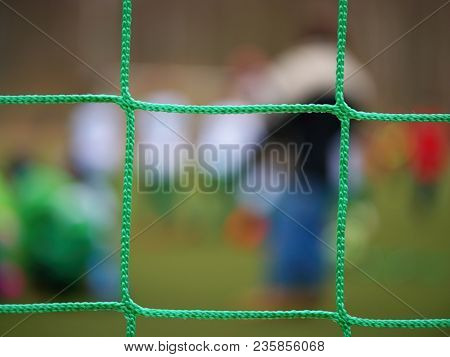 Football Player Stands Against Goal With Net And Stadium. Football Gate Net. Soccer Gate Net.  In Bl