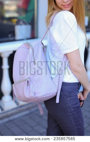 Beautiful girl standing with light pink backpack. Concept of strolling in city and fashion look. poster