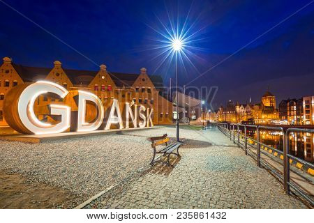 Gdansk, Poland - April 5, 2018: Illuminated Gdansk city sign at Motlawa river, Poland. Gdansk is the historical capital of Polish Pomerania with medieval old town architecture.