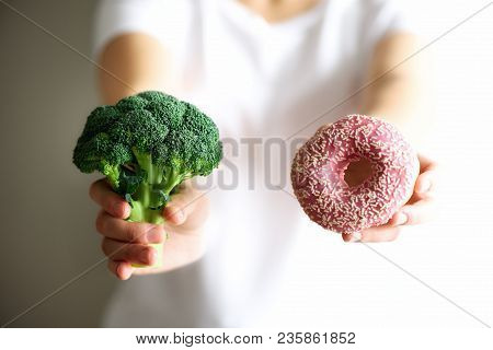 Young Woman In White T-shirt Choosing Between Broccoli Or Junk Food, Donut. Healthy Clean Detox Eati