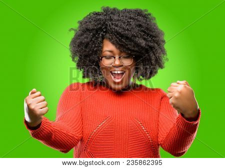 Beautiful african woman happy and excited celebrating victory expressing big success, power, energy and positive emotions. Celebrates new job joyful