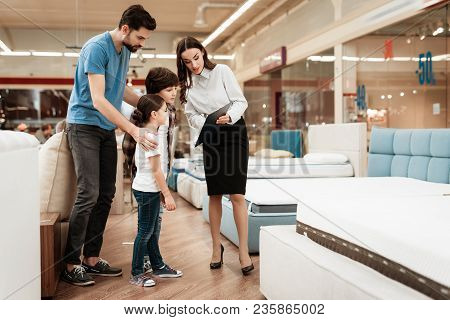 White Woman Consultant Demonstrates Orthopedic Mattress To Young Father With Children In Furniture S