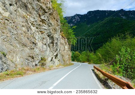 Mountain Road In Montenegro, Sharp Turn At Steep Rock. Mountains Covered With Lush Green Vegetation