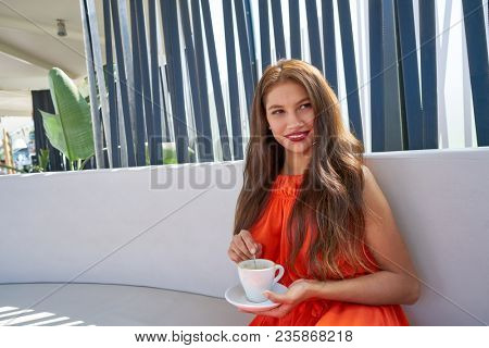 Young latin woman having coffee in lounge bar outdoor