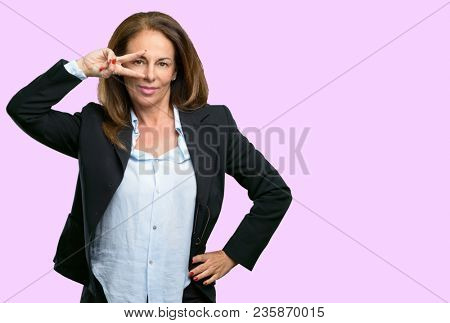 Middle age business woman looking at camera through her fingers