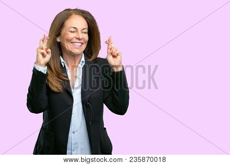 Middle age business woman with crossed fingers asking for good luck