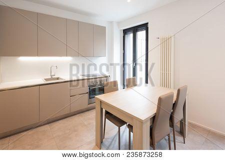 Modern minimalist kitchen with large tiles. Nobody inside