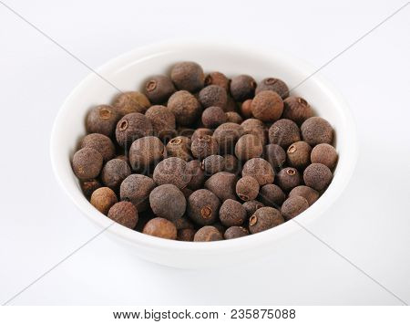 bowl of allspice berries on white background