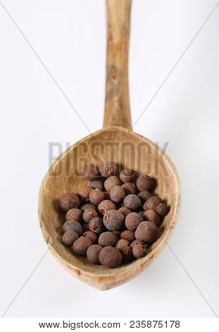 spoon of whole allspice berries on white background