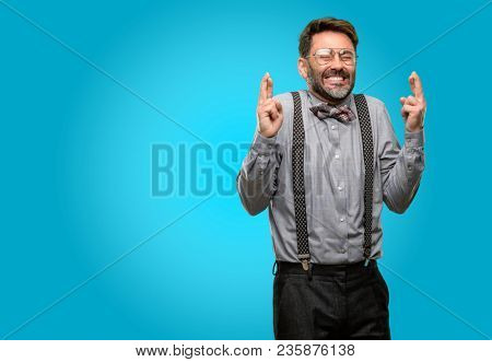 Middle age man, with beard and bow tie with crossed fingers asking for good luck