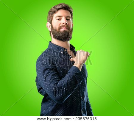 Young hipster man with big beard proud, excited and arrogant, pointing with victory face over green background