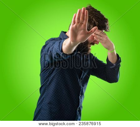 Young hipster man with big beard stressful and shy keeping hand on head, tired and frustrated over green background