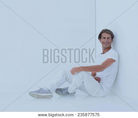 pensive boy sitting near the wall
