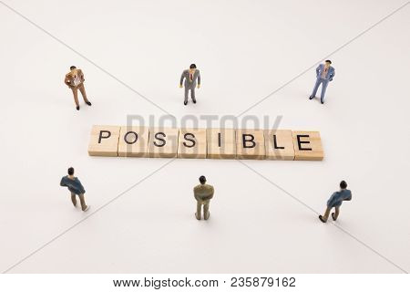 Miniature Figures Businessman : Meeting On Possible Word By Wooden Block Word On White Paper Backgro