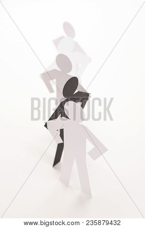 Linked Line Of Five  Paper Standing Figure With Black One On Bright White Background. In Concept Of