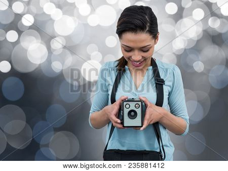 happy photographer with vintage camera. Silver bokeh behind