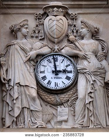 PARIS, FRANCE - JANUARY 05: Two muses support the clock, topped by the coat of arms of Cardinal Richelieu, facade of the Saint Ursule chapel of the Sorbonne in Paris, France on January 05, 2018.