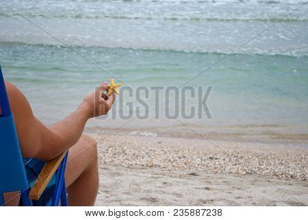Young Man Guy Sitting On A Deckchair On The Shore Holding A Yellow Starfish In His Hand, Resting Sun