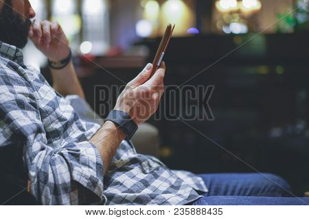 Handsome Bearded Man Using Electronic Reader Book Computer While Resting In Lobby Hotel. Man Using E