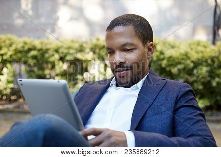 Young American African Businessman In Informal Clothes Working At Sunny Street On Electronic Touch P