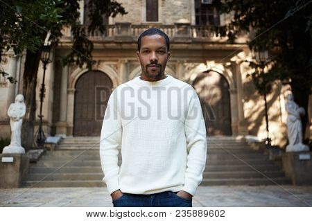 Portrait Of Pensive Cute Young African-american Hipster In Informal White Jersey Walking At Sunny Ci