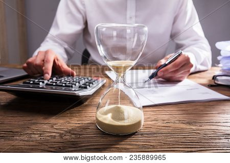 Businessperson's Hand Calculating Invoice In Office