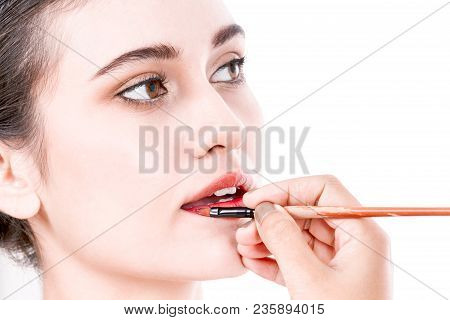 Stylist Applying Red Lip Gloss To The Beautiful Woman