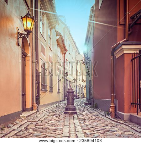 Fantasy Image With Narrow Medieval Street In Medieval Part Of Riga City, Where Numerous Tourists Can
