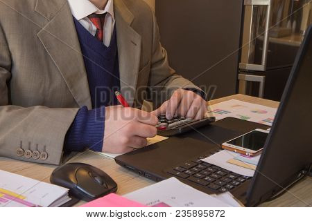 Hands Of Accountant With Calculator And Pen. Accounting Background. Businessman Using A Calculator T