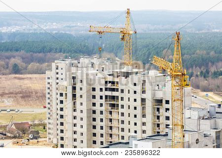 Panoramic View On Tower Cranes And Unfinished Multi-storey High Near Buildings Under Construction Si
