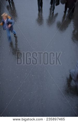 A Passer-by In Color Hurts In The Rain Among Black Silhouettes And Shadows On Black Wet Asphalt. Blu