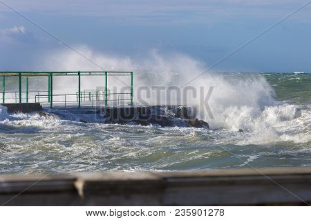 Sea Waves Breaking Against Seashore Promenade In Windy Day: Stormy Weather.