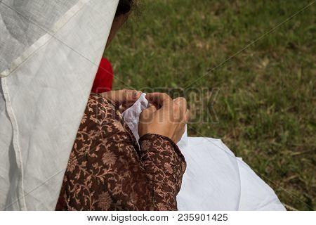 Woman With Renaissance Dress Doing Needlework Outdoors.