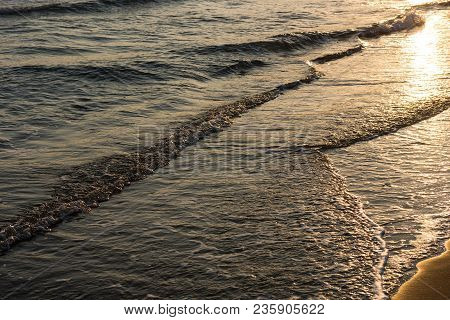 Waves Approaching Sandy Beach During The Sunset