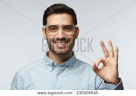 Young Man Having Happy Look, Smiling, Gesturing, Showing Ok Sign, Showing Ok-gesture With His Finger