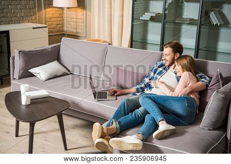 Happy Couple Hugging Each Other And Having Fun With Laptop In Living Room