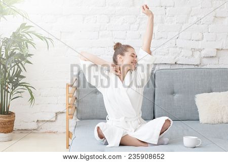 Young Girl Sits Stretching In Bed, Wake Up Early In The Morning, Sunrise Mood In White Loft Apartmen