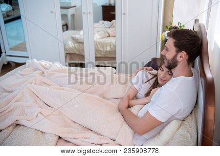 Side View Of Young Couple Lying In Modern Bedroom