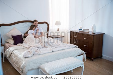 Young Woman Lying On Her Boyfriend Chest In Bedroom With Modern Interior