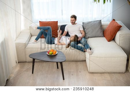 Woman Using Digital Tablet And Lying On Her Boyfriend Knees In Modern Modern