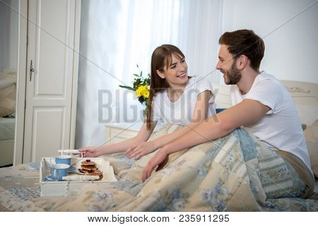 Smiling Couple Sitting On Bed With Breakfast On Tray In Bedroom With Modern Interior