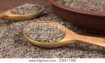 Cumin Dry Seeds Into A Bowl On A Wooden Table. Cumin Seeds In Wooden Spoon