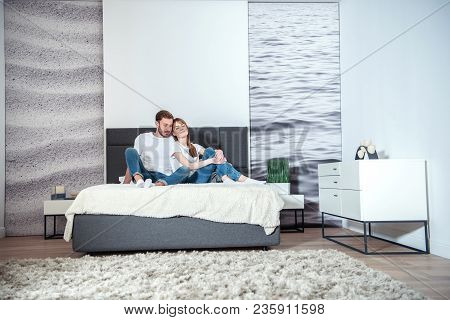 Young Male Hugging His Girlfriend In Bedroom With Design Interior