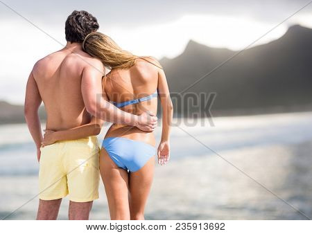 Back of couple in swimsuits against blurry beach