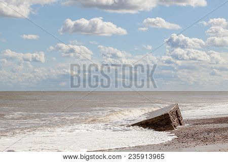 D-day Normandy Landings. Pretty Coastal Landscape With Clouds And Partially Buried Ww2 Beach Defense