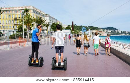NICE, FRANCE - JUNE 4, 2017: People walking and riding segways at the famous Promenade des Anglais bordering the Mediterranean sea in Nice, in the French Riviera, France
