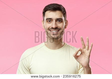 Caucasian Male Showing Ok-gesture With His Fingers. Young Man In Beige Tshirt Having Happy Look, Smi