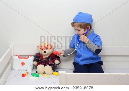 Health Care Concept. Medical Examination Of Ill Teddy Bear In Bed. White Teddy Bear In Pediatrician'