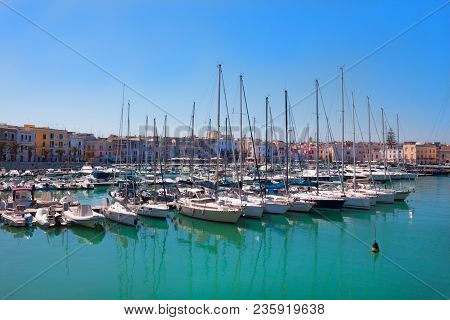 Many Beautiful White Sailing Yachts Parked On The Seashore Against The Background Of The Cityscape O